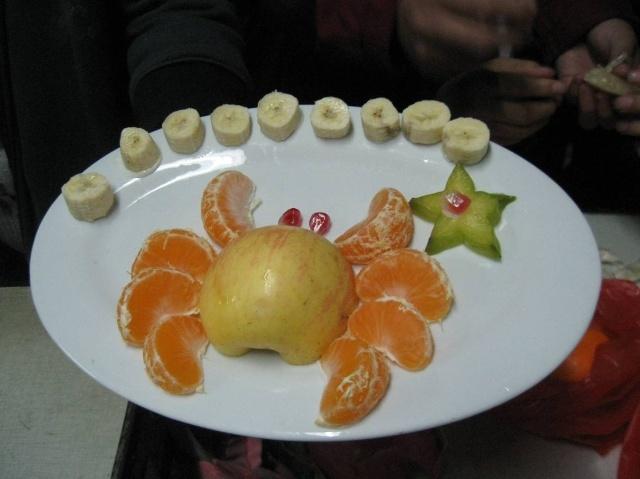 水果拼盘很容易做,就是选择色彩鲜艳的各色水果切成片或块甚至切成花样状,在一个漂亮的盘子里摆放成图案状就可以了。 比如水果颜色的选择: 红色:西瓜,草莓,樱桃,圣女果... 黄色:香蕉,菠萝,黄桃,杏,芒果,木瓜... 白色:梨,荔枝,荸荠... 绿色:杨桃,猕猴桃, 紫色:李子, 水果拼盘的关键是搭配色彩和图案,要凭想象和有点艺术感。 来看看我们自己设计的水果拼盘罗!看我的螃蟹腿是用橘子做的哦,杨桃做的海星哦.