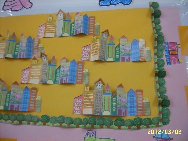 """主题墙分三个内容:一是""""美丽的家园"""",展示幼儿用不同材料制作的房子"""
